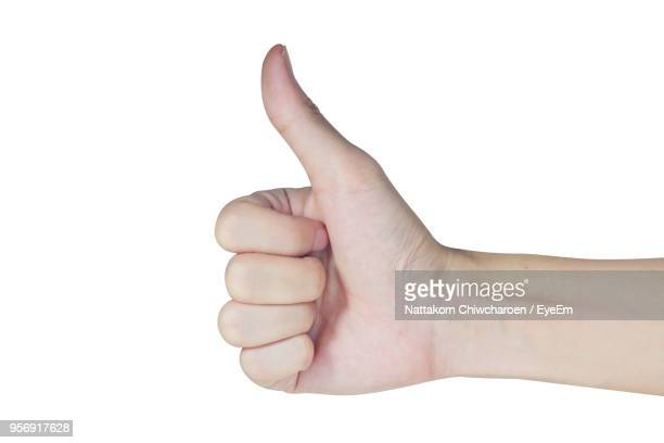 cropped hand showing thumbs up against white background - thumbs up stock pictures, royalty-free photos & images