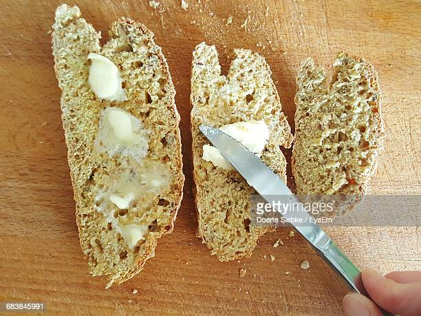 cropped hand spreading butter on bread at home - spreading stock pictures, royalty-free photos & images