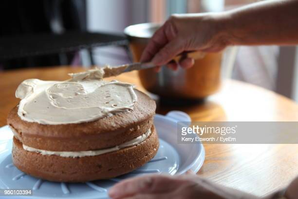 cropped hand spreading cream on cake - sponge cake stock pictures, royalty-free photos & images