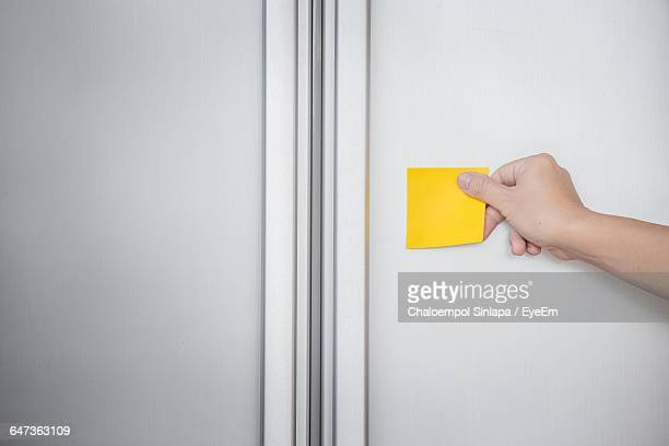 cropped hand sticking adhesive note on refrigerator - stick stock-fotos und bilder