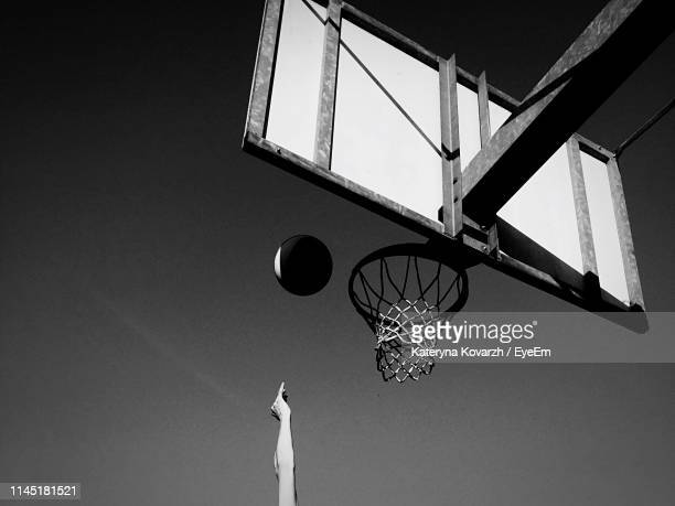 cropped hand throwing ball in basketball hoop against sky - ゴールを決める ストックフォトと画像