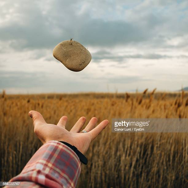 Cropped Hand Throwing Stone On Field Against Sky
