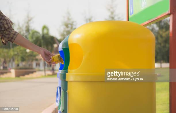 Cropped Hand Throwing Waste In Dustbin