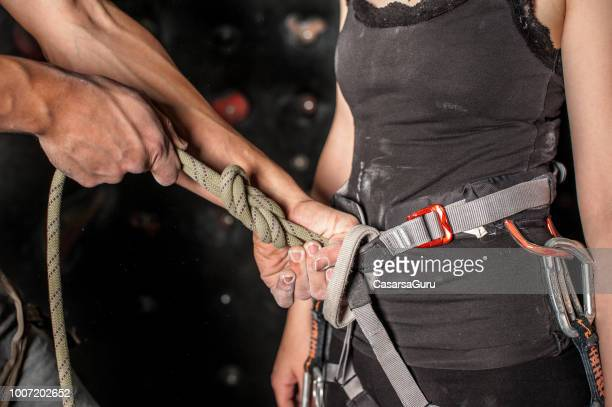 cropped hand tighten the knot on the climbing rope - tighten stock photos and pictures
