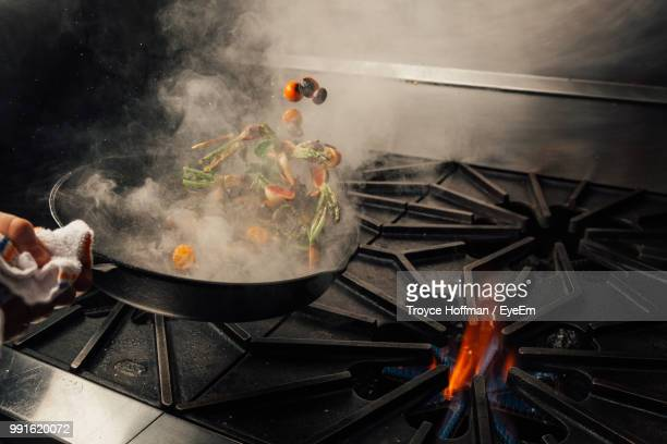 cropped hand tossing vegetables in cooking pan over stove in kitchen at home - lanciare foto e immagini stock