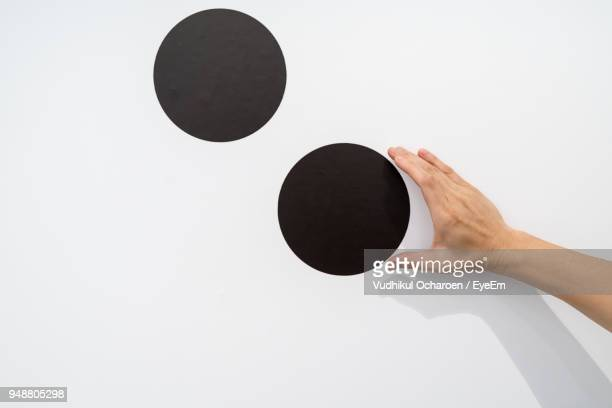cropped hand touching black spot on white wall - spotted stockfoto's en -beelden