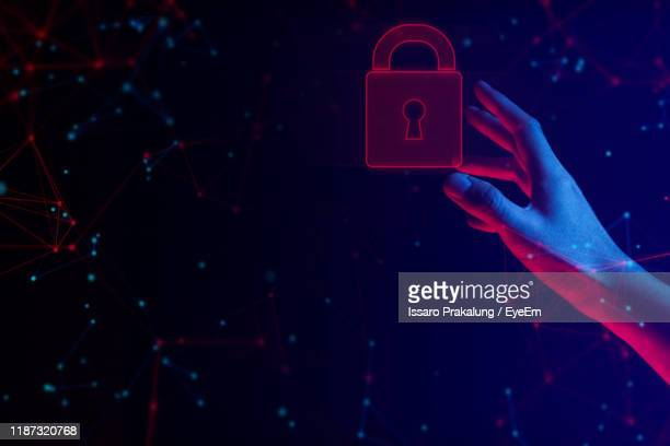 cropped hand touching digital padlock with surrounded connected dots against abstract background - umgeben stock-fotos und bilder
