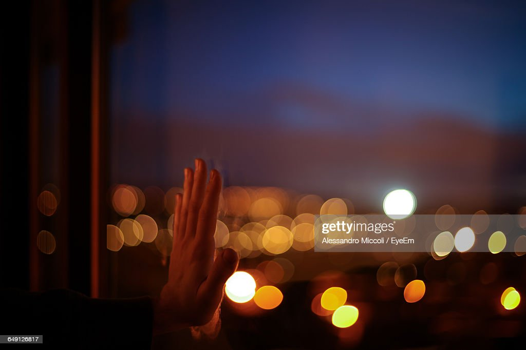 Cropped Hand Touching Glass Window Against Defocused Light At Dusk : Stock Photo