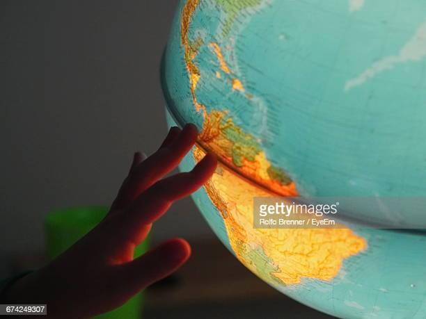Cropped Hand Touching Illuminated Globe In Room
