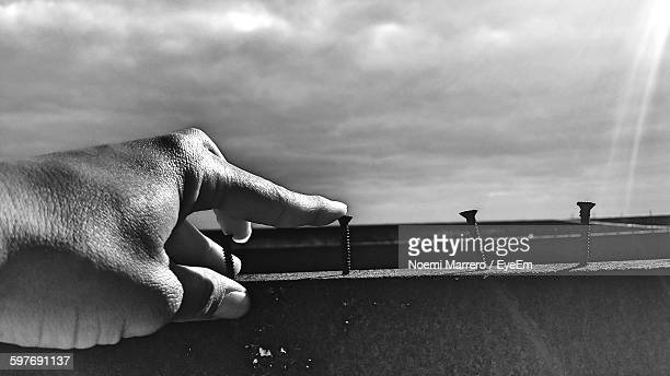 cropped hand touching nails on wood against sky - noemi foto e immagini stock