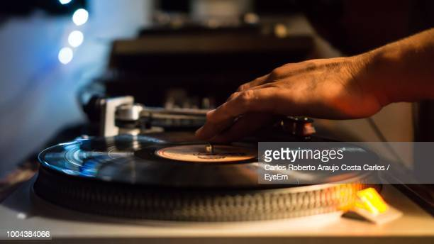 cropped hand touching record playing on turntable - draaitafel stockfoto's en -beelden