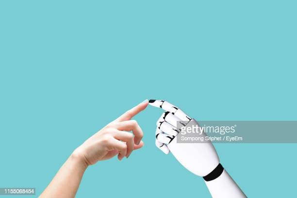 cropped hand touching robot against turquoise background - robot stock pictures, royalty-free photos & images
