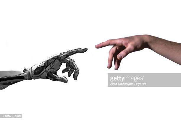 cropped hand touching robot against white background - robô - fotografias e filmes do acervo