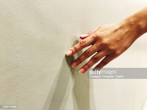 cropped hand touching wall - touching stock photos and pictures