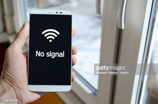 cropped hand using mobile phone with text by window - radio wave stock pictures, royalty-free photos & images