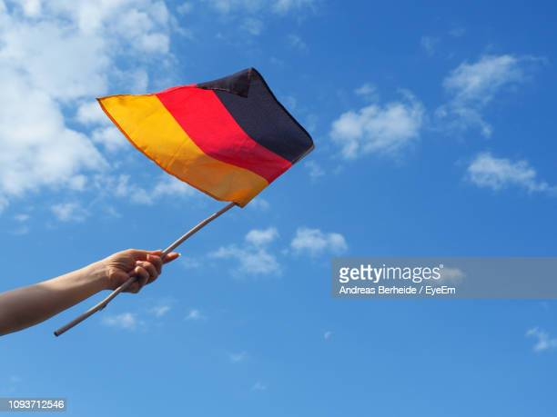 cropped hand waving german flag against sky - german flag stock pictures, royalty-free photos & images