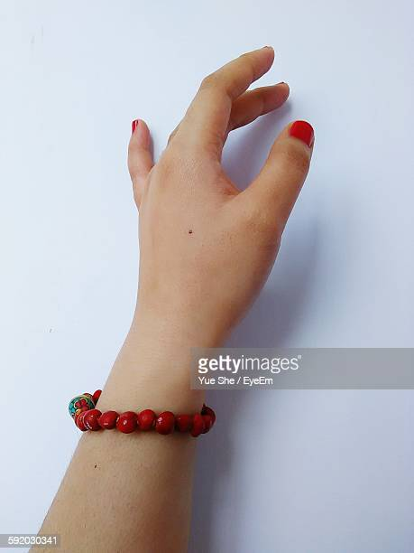 Cropped Hand Wearing Bracelet Against White Background