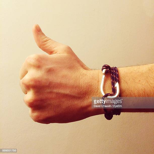 cropped hand wearing bracelet gesturing thumbs up against wall - chauvin stock pictures, royalty-free photos & images