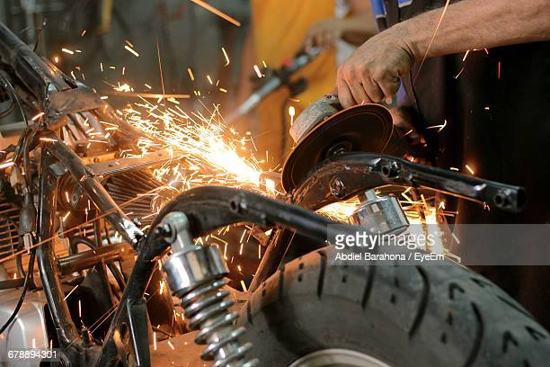 Cropped Hand Welding Parts In Motorcycle Repair Workshop
