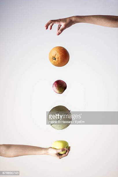 Cropped Hand With Apple Below Various Fruits Being Dropped By Friend Against White Background