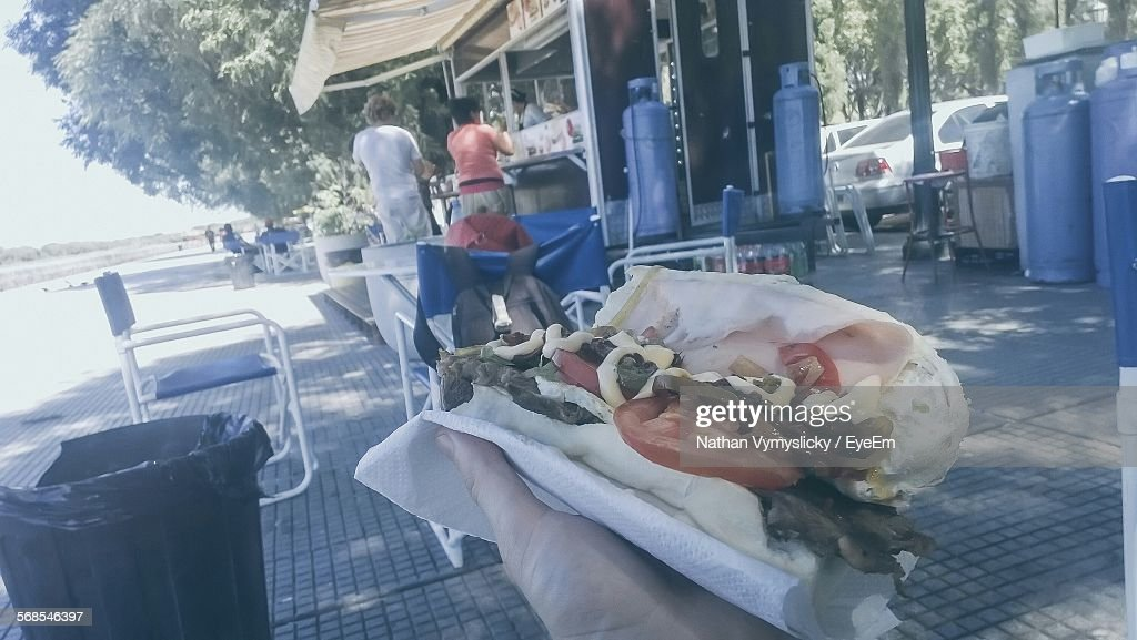 Cropped Hand With Baguette Sandwich On Street : Stock Photo
