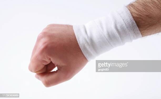 cropped hand with bandage against white background - bandagem - fotografias e filmes do acervo