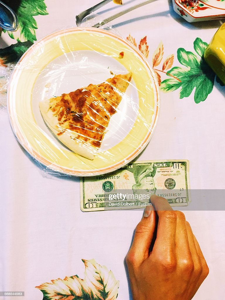 Cropped Hand With Dollar Bill By Pizza Served On Plate In Restaurant : Stock Photo