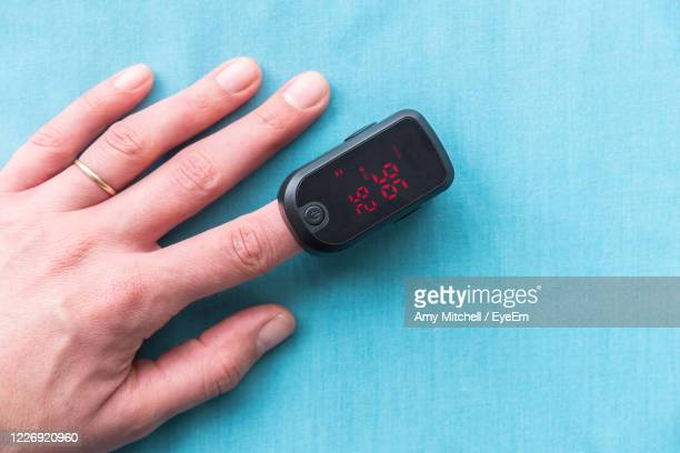 cropped hand with pulse oxymeter on table - pulse oximeter stock pictures, royalty-free photos & images