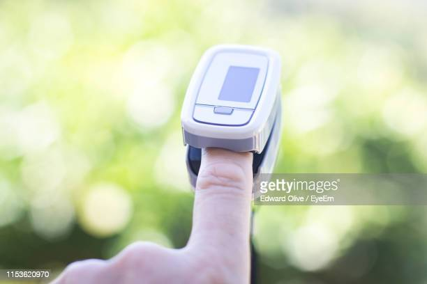 cropped hand with pulse oxymeter - pulse oximeter stock pictures, royalty-free photos & images