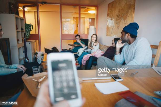 Cropped hand woman holding mobile phone against friends in college dorm room