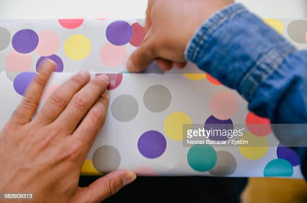 Cropped Hand Wrapping Gift With Polka Dot Paper