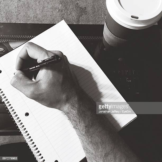 Cropped Hand Writing On Spiral Notebook By Coffee On Table