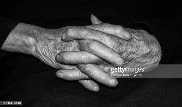 cropped hands against black background - black and white hands stock pictures, royalty-free photos & images