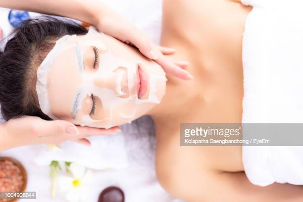 Cropped Hands Applying Face Mask To Woman At Beauty Spa