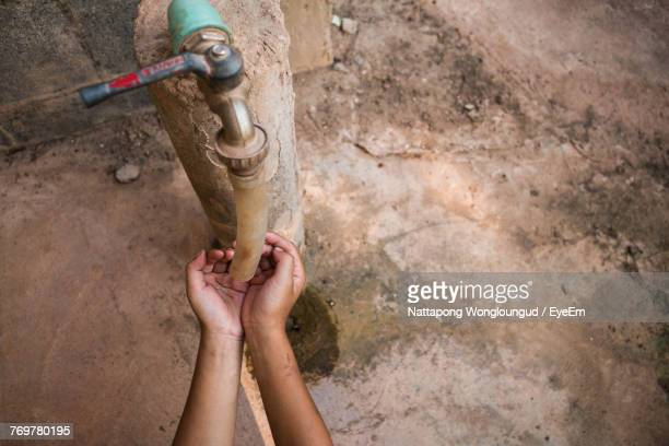 Cropped Hands Below Faucet During Drought
