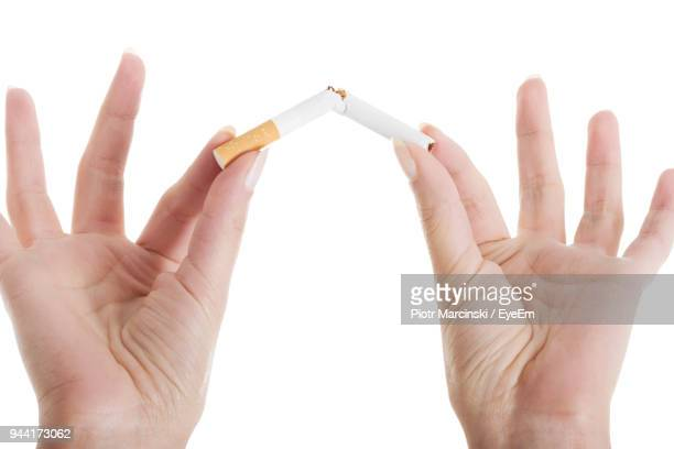 Cropped Hands Breaking Cigarette Against White Background