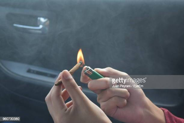cropped hands burning marijuana joint in car - smoking weed stock photos and pictures