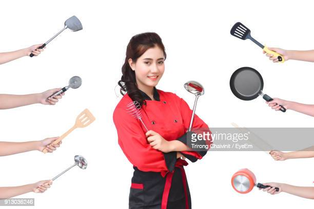 Cropped Hands By Portrait Of Smiling Young Woman Holding Kitchen Utensils Against White Background