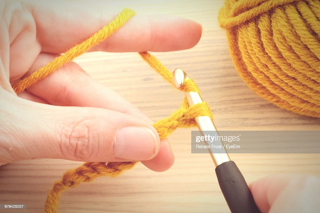 Cropped Hands Crocheting Wool Over Table : Stock Photo