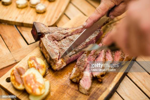Cropped Hands Cutting Meat