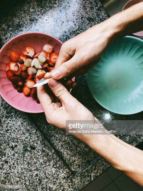 cropped hands cutting strawberries at table - marrom stock pictures, royalty-free photos & images