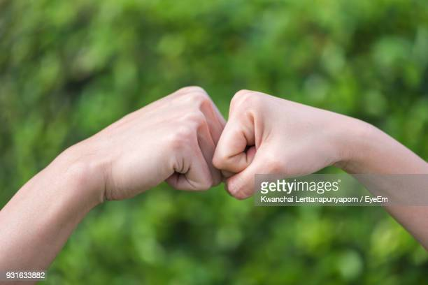 cropped hands doing fist bump - fist bump stock pictures, royalty-free photos & images