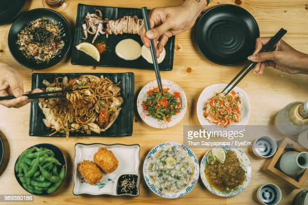cropped hands eating food on dining table - thai food stock pictures, royalty-free photos & images