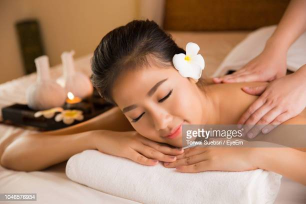 cropped hands giving massage to young woman lying on bed in spa - torwai stock pictures, royalty-free photos & images