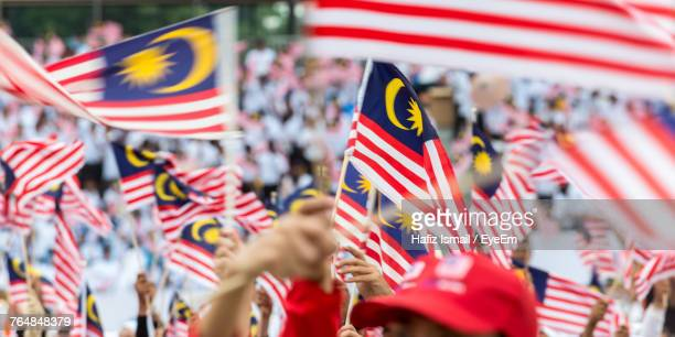cropped hands holding american flags on street - malaysia stock pictures, royalty-free photos & images