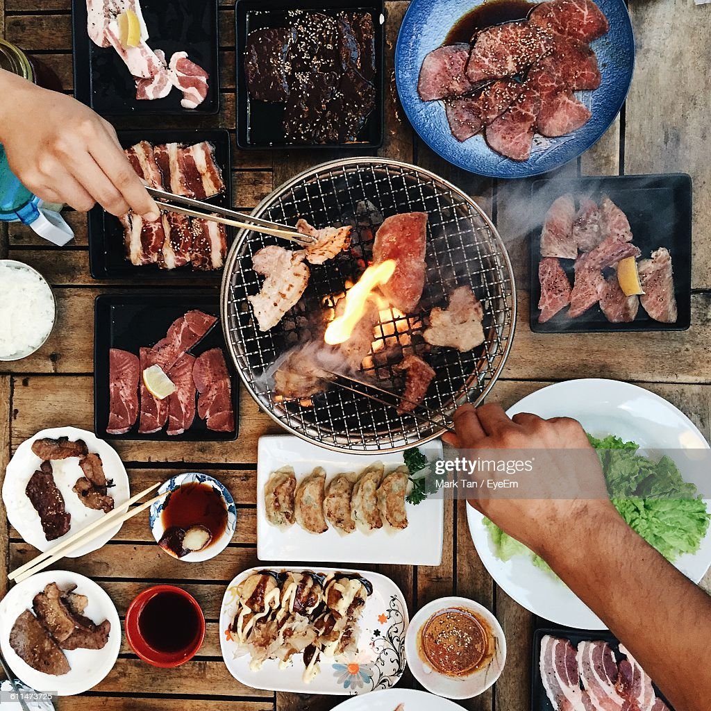 Cropped Hands Holding Barbecuing Meat On Grill With Tongs : Stock Photo