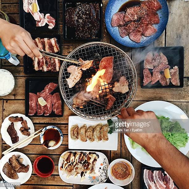 Cropped Hands Holding Barbecuing Meat On Grill With Tongs