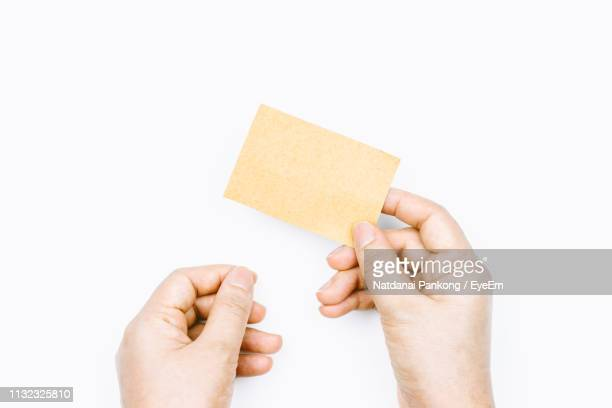 cropped hands holding blank business card against white background - 名刺 ストックフォトと画像
