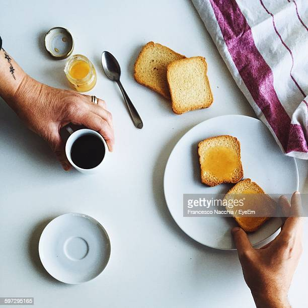 Cropped Hands Holding Bread And Coffee On Table At Home