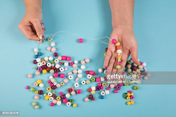 cropped hands holding colorful beads at table - bead stock pictures, royalty-free photos & images